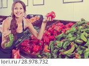 Купить «Woman seller wearing apron holding red and green paprika», фото № 28978732, снято 18 июля 2019 г. (c) Яков Филимонов / Фотобанк Лори