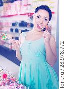 Купить «Positive girl in the shop taking candy in hands», фото № 28978772, снято 25 апреля 2017 г. (c) Яков Филимонов / Фотобанк Лори