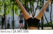 Купить «Slender girl in a black sports suit stands on her head and does leg exercises in the park», видеоролик № 28981556, снято 18 марта 2019 г. (c) Константин Шишкин / Фотобанк Лори