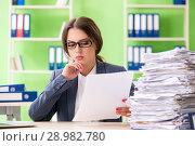 Купить «The young female employee very busy with ongoing paperwork», фото № 28982780, снято 8 июня 2018 г. (c) Elnur / Фотобанк Лори