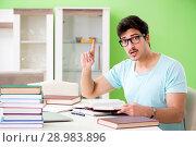 Купить «Student preparing for university exams at home», фото № 28983896, снято 19 мая 2018 г. (c) Elnur / Фотобанк Лори