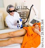 Купить «Woman removing hair from legs with laser», фото № 28985364, снято 27 февраля 2020 г. (c) Яков Филимонов / Фотобанк Лори