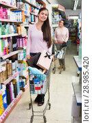 Купить «Young smiling woman standing with shopping cart», фото № 28985420, снято 22 октября 2018 г. (c) Яков Филимонов / Фотобанк Лори