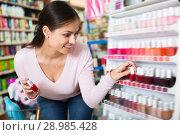 Купить «Happy woman picking nail varnish from shelf», фото № 28985428, снято 26 июня 2019 г. (c) Яков Филимонов / Фотобанк Лори