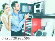 Купить «Couple choosing microwave in household appliance section», фото № 28985596, снято 15 июня 2017 г. (c) Яков Филимонов / Фотобанк Лори