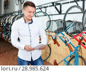 Smiling man is choosing modern bicycle with bike characteristic in the bike store. Стоковое фото, фотограф Яков Филимонов / Фотобанк Лори