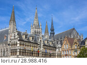 Купить «Detail of traditional Flemish architecture in the restored Cloth Hall, Grote markt, Ypres, Belgium with the spire of St Martens Kathedraal behind.», фото № 28988416, снято 5 июля 2018 г. (c) age Fotostock / Фотобанк Лори