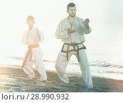 Купить «Man and boy exercising karate», фото № 28990932, снято 12 июля 2017 г. (c) Яков Филимонов / Фотобанк Лори