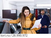 Купить «Young woman is disappointed of tire replacement of her car in winter», фото № 28990972, снято 18 декабря 2017 г. (c) Яков Филимонов / Фотобанк Лори