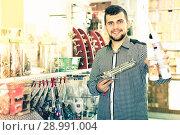 Купить «cheerful male customer examining various glue tubes in store», фото № 28991004, снято 5 апреля 2017 г. (c) Яков Филимонов / Фотобанк Лори