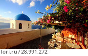 Blue church dome with wind playing with colorful flower shrub on a terrace of traditional cafeteria in typical greek village of Oia, Santorini island, Greece. Стоковое видео, видеограф Matej Kastelic / Фотобанк Лори