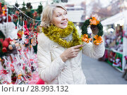Купить «Smiling woman is buying Christmas wreath in the market», фото № 28993132, снято 21 декабря 2017 г. (c) Яков Филимонов / Фотобанк Лори