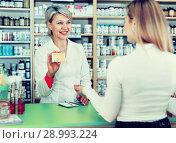 Купить «Mature female seller suggesting care products to young customer», фото № 28993224, снято 15 марта 2017 г. (c) Яков Филимонов / Фотобанк Лори