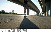 Купить «Cute girl riding a skateboard under the bridge in the evening, the sun shines», видеоролик № 28993708, снято 11 июля 2020 г. (c) Константин Шишкин / Фотобанк Лори