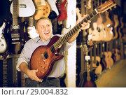 Купить «Man choosing electric guitar», фото № 29004832, снято 18 сентября 2017 г. (c) Яков Филимонов / Фотобанк Лори