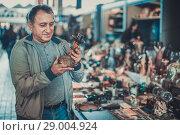 Купить «Positive senior man choosing vintage goods at flea market», фото № 29004924, снято 23 октября 2017 г. (c) Яков Филимонов / Фотобанк Лори