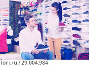 Купить «female seller demonstrating sneakers to customer in sports store», фото № 29004984, снято 22 ноября 2016 г. (c) Яков Филимонов / Фотобанк Лори