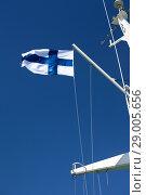 Национальный флаг Финляндии развевается на мачте парома на фоне голубого неба. Стоковое фото, фотограф Кекяляйнен Андрей / Фотобанк Лори