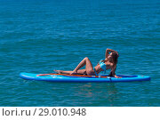 Woman relaxing on a SUP boarding in the sea. Healthy lifestyle in harmony with nature. Стоковое фото, фотограф Константин Сиятский / Фотобанк Лори