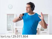 Купить «Young handsome man singing karaoke at home», фото № 29011864, снято 15 ноября 2017 г. (c) Elnur / Фотобанк Лори