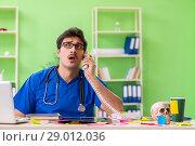 Купить «Young doctor sitting in hospital with many conflicting prioritie», фото № 29012036, снято 18 мая 2018 г. (c) Elnur / Фотобанк Лори