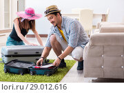 Купить «Young family packing for vacation travel», фото № 29012616, снято 30 апреля 2018 г. (c) Elnur / Фотобанк Лори