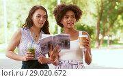 Купить «women with city guide and drinks on street», видеоролик № 29020672, снято 15 августа 2018 г. (c) Syda Productions / Фотобанк Лори