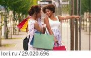 Купить «women with shopping bags looking at shop window», видеоролик № 29020696, снято 15 августа 2018 г. (c) Syda Productions / Фотобанк Лори