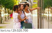 Купить «women with shopping bags looking at shop window», видеоролик № 29020700, снято 15 августа 2018 г. (c) Syda Productions / Фотобанк Лори