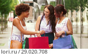 Купить «happy women showing shopping bags in city», видеоролик № 29020708, снято 15 августа 2018 г. (c) Syda Productions / Фотобанк Лори
