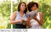 Купить «women with city guide and drinks on street», видеоролик № 29020728, снято 15 августа 2018 г. (c) Syda Productions / Фотобанк Лори
