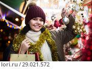 Купить «girl choosing Christmas decoration at market», фото № 29021572, снято 12 декабря 2016 г. (c) Яков Филимонов / Фотобанк Лори