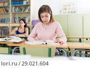Купить «Girl is sitting at the desk and writing homework», фото № 29021604, снято 23 марта 2018 г. (c) Яков Филимонов / Фотобанк Лори