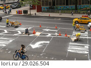 Купить «Employees from the New York City Department of Transportation install new thermoplastic lane markings after a recent re-paving on Ninth Avenue in the Chelsea...», фото № 29026504, снято 20 июня 2018 г. (c) age Fotostock / Фотобанк Лори