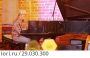 Купить «Gray-haired man with a tail on his head with glasses playing the piano in a jazz bar», видеоролик № 29030300, снято 22 июля 2019 г. (c) Константин Шишкин / Фотобанк Лори