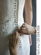 Купить «The mother of the bride helps her daughter button the wedding dress, Valencia, Spain», фото № 29034056, снято 15 октября 2016 г. (c) age Fotostock / Фотобанк Лори
