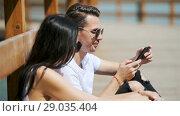 Купить «Picture of a joyful couple using smartphones in the park», видеоролик № 29035404, снято 31 июля 2018 г. (c) Дмитрий Травников / Фотобанк Лори