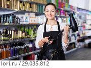Купить «Young woman hairstylist holding blow dryer and hair cutters in cosmetics salon», фото № 29035812, снято 31 марта 2018 г. (c) Яков Филимонов / Фотобанк Лори