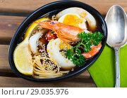 Купить «Image of spicy pan-Asian soup with squid, shrimp, egg noodles and sesame», фото № 29035976, снято 21 октября 2018 г. (c) Яков Филимонов / Фотобанк Лори