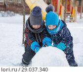Купить «Two nice children boys 2 and 4 years in winter roll big snowball on playground», фото № 29037340, снято 21 марта 2018 г. (c) Юлия Бабкина / Фотобанк Лори