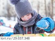 Купить «Мальчик 4 года зимой на детской площадке играет кубиками с цифрами, Портрет, крупный план», фото № 29037348, снято 21 марта 2018 г. (c) Юлия Бабкина / Фотобанк Лори