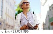 Купить «senior woman or tourist walking with city guide», видеоролик № 29037996, снято 21 августа 2018 г. (c) Syda Productions / Фотобанк Лори