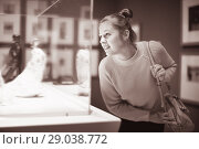 Купить «Young female visitor looking at exhibition in museum of ancient sculpture», фото № 29038772, снято 18 ноября 2017 г. (c) Яков Филимонов / Фотобанк Лори