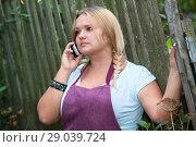 Купить «Девушка разговаривает по мобильному телефону во дворе дома», фото № 29039724, снято 9 августа 2014 г. (c) Кекяляйнен Андрей / Фотобанк Лори