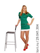 Купить «Симпатичная девушка в коротком зеленом платье около стула», фото № 29041304, снято 7 декабря 2013 г. (c) Александр Гаценко / Фотобанк Лори