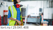 Купить «Composite image of female architect holding blueprint against grey background», фото № 29041408, снято 15 декабря 2018 г. (c) Wavebreak Media / Фотобанк Лори