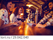 Купить «Young women interacting with bartender at counter», фото № 29042040, снято 20 октября 2018 г. (c) Wavebreak Media / Фотобанк Лори