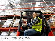 Купить «male worker driving forklift loader at warehouse», фото № 29042756, снято 9 декабря 2015 г. (c) Syda Productions / Фотобанк Лори