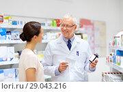 Купить «apothecary and woman with drug at pharmacy», фото № 29043216, снято 27 июня 2015 г. (c) Syda Productions / Фотобанк Лори