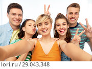 Купить «happy friends taking selfie and showing peace», фото № 29043348, снято 30 июня 2018 г. (c) Syda Productions / Фотобанк Лори